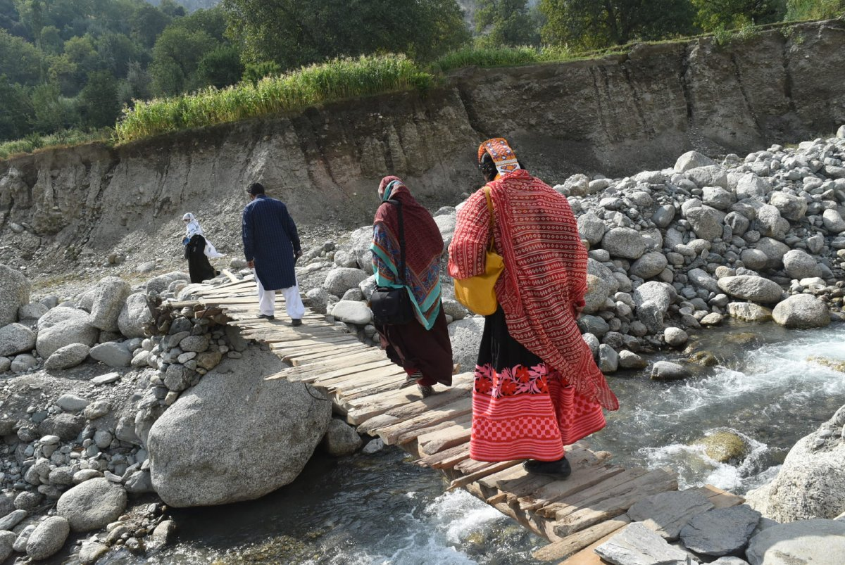 In Chitral, Pakistan (2017): A drug distribution team led by their health supervisor crosses a narrow wooden foot bridge over a stream to get to Bhimbeer village in Chitral district. Pakistan launched their first-ever Mass Drug Administration to eliminate trachoma in Chitral district in September 2017 with support from CBM and The Fred Hollows Foundation. Zahid Awan captured this moment while working for CBM.