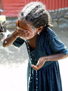 """Clean Face: Healthy Eyes!"" A young girl in Amhara, Ethiopia washes her face with soap and water, because facial cleanliness is key to fighting trachoma. With support from the Lions/Carter Center Sight First Initiative, the Amhara Regional Health and Education Bureaus have implemented a state-wide school-based health education program, teaching the next generation how to prevent trachoma. Photographer: Kenya Casey"