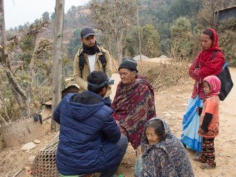 Members of the survey team, Bishal Dhakal and Shravan Subedi, check the eye of Radha Thapa for clinical signs of trachoma.