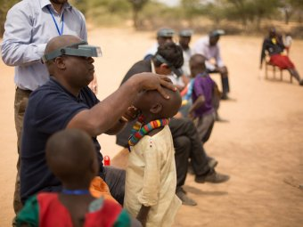 Jeremiah Ngondi, a Master Grader with RTI International, examines a child's eyes for trachoma. Photo: RTI International